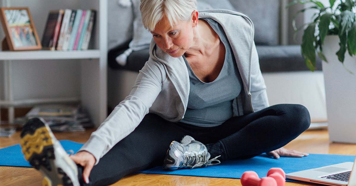 Mature woman stretching on a yoga mat