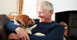 Senior man is holding his dog