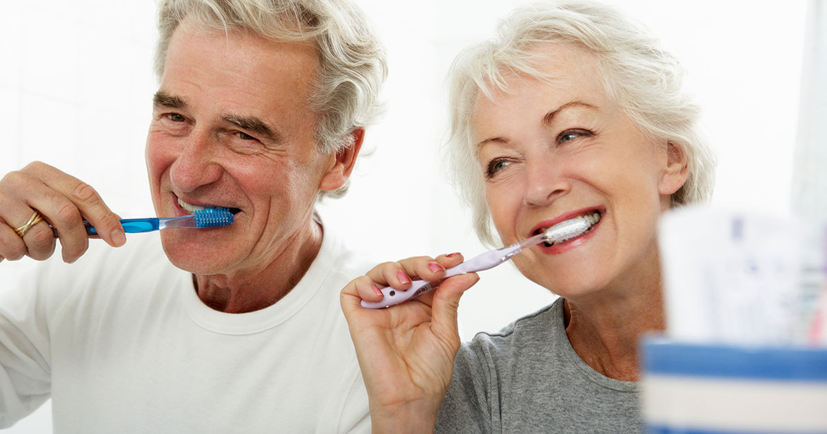 A senior couple are brushing their teeth together