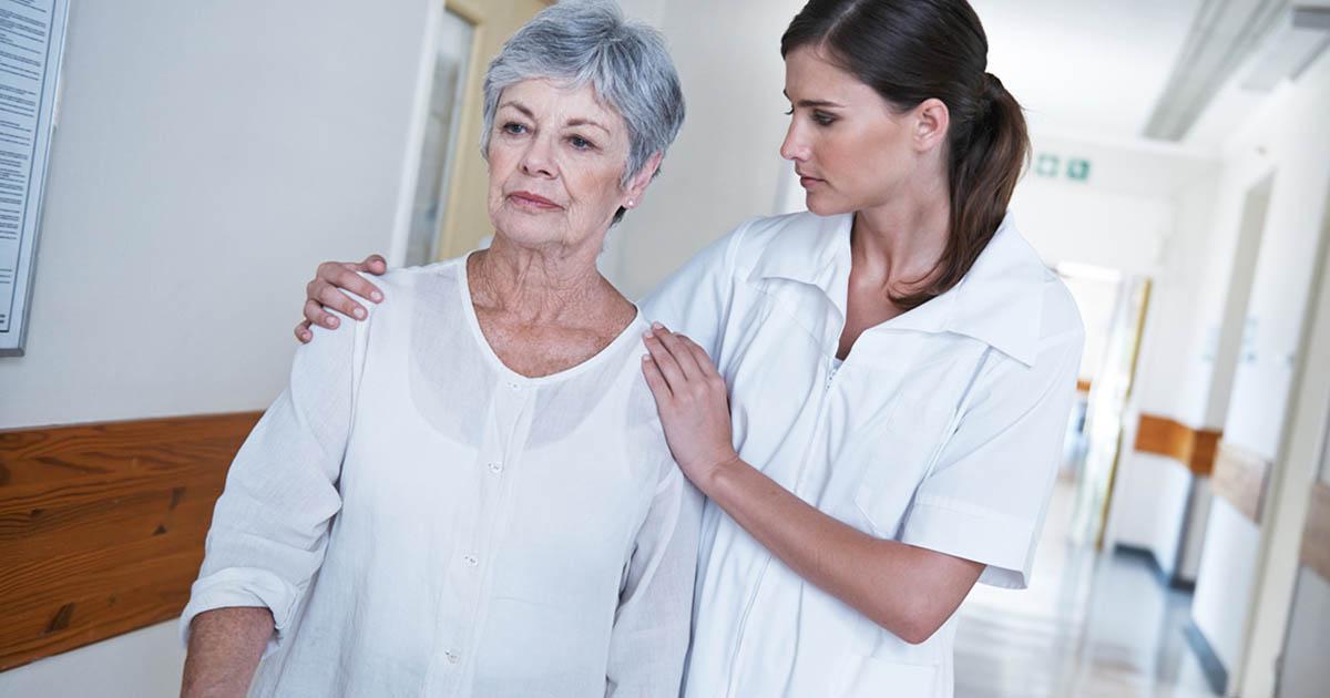 Patient and nurse walking down a hospital corridor