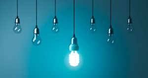 One hanging energy saving light bulb glowing stand out from unlit incandescent bulbs