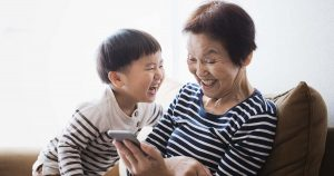 An asian senior woman and her grand son using a smartphone together