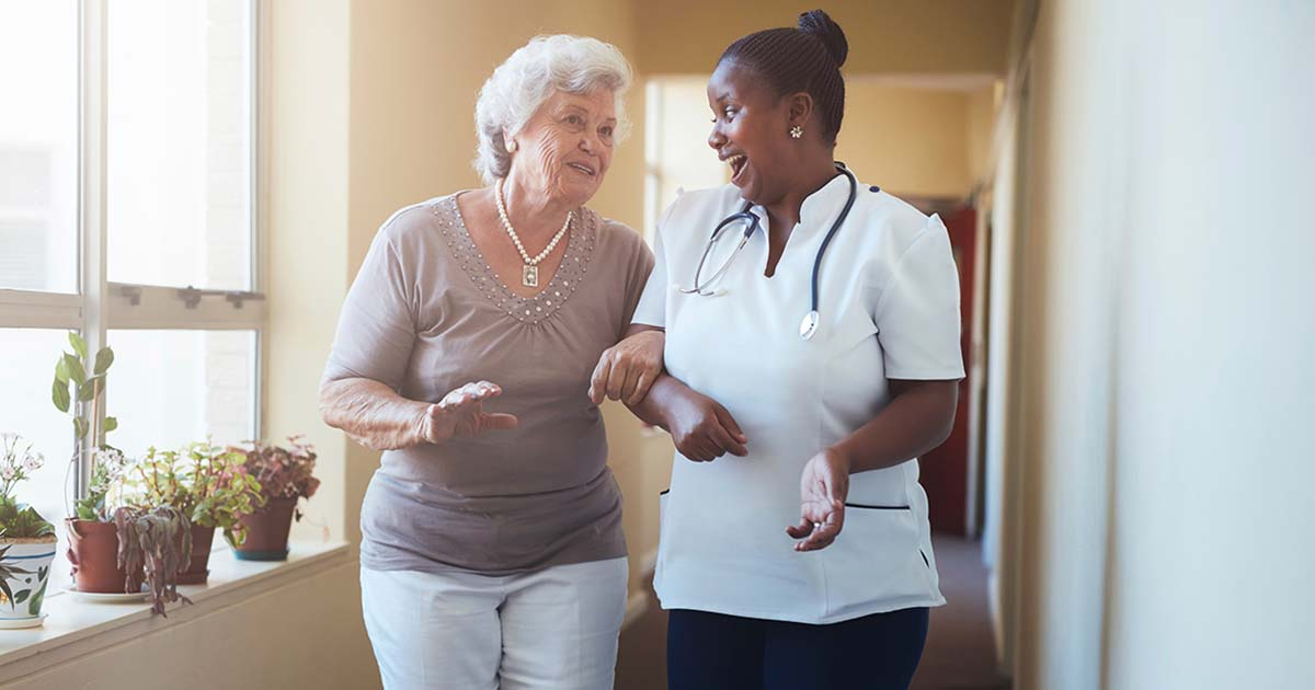 Nursing home resident and nurse walking together