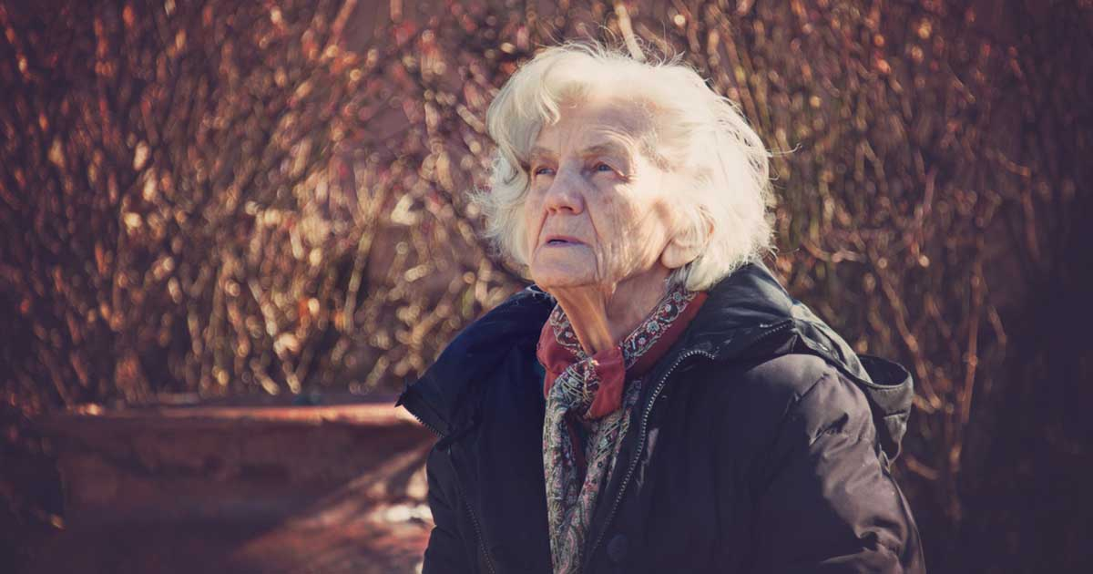 Elderly woman outside looking confused