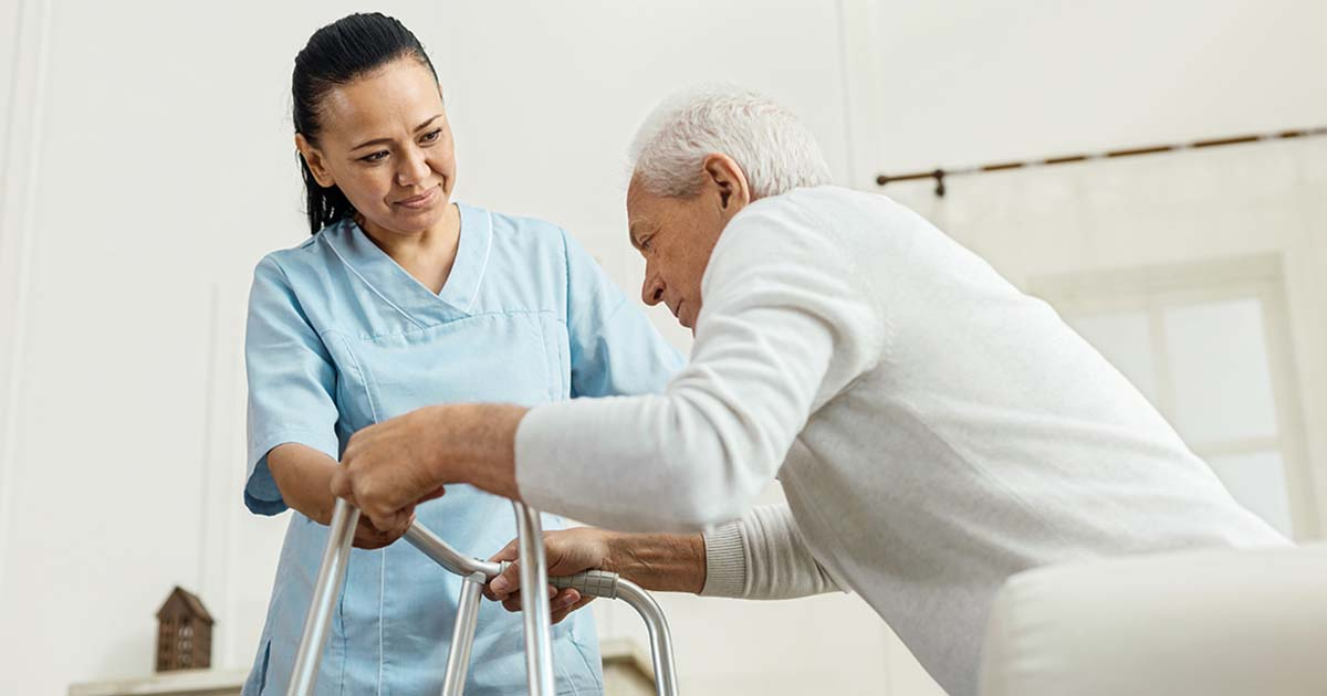 Caregiver is helping elderly man with his walker