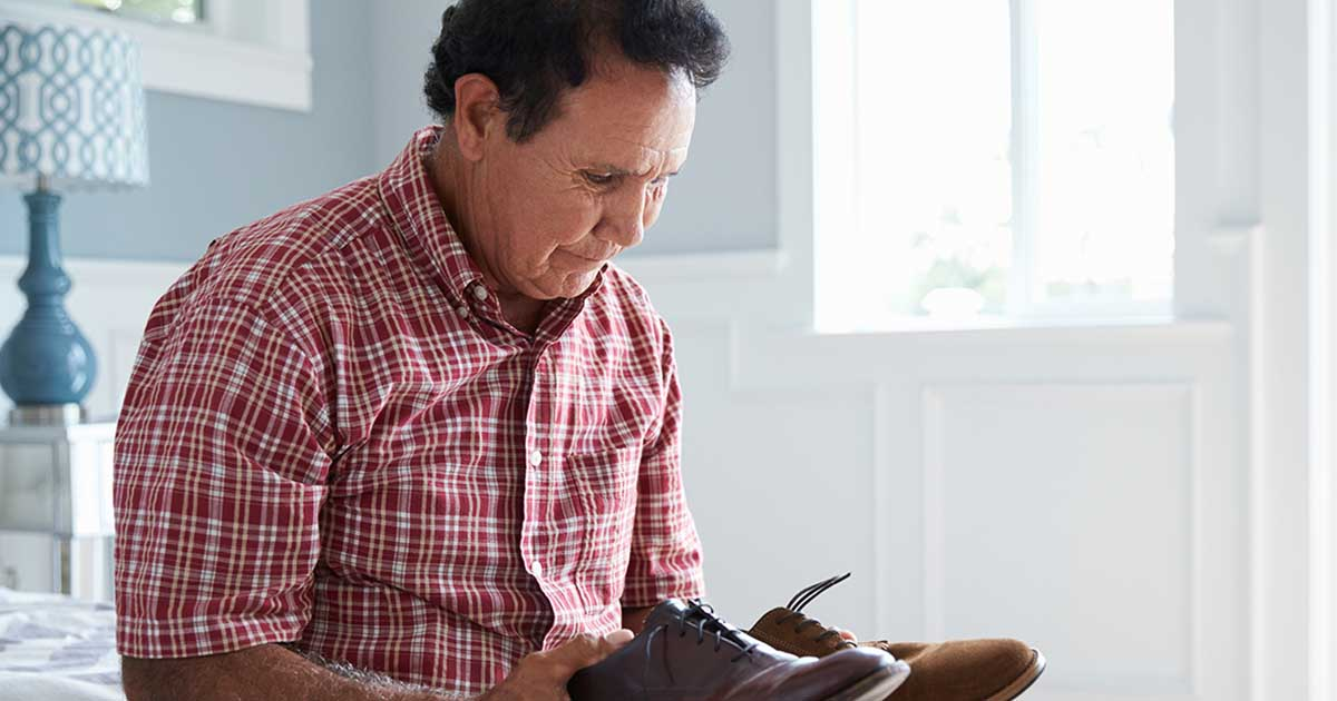 Mature man looking at two different colored shoes