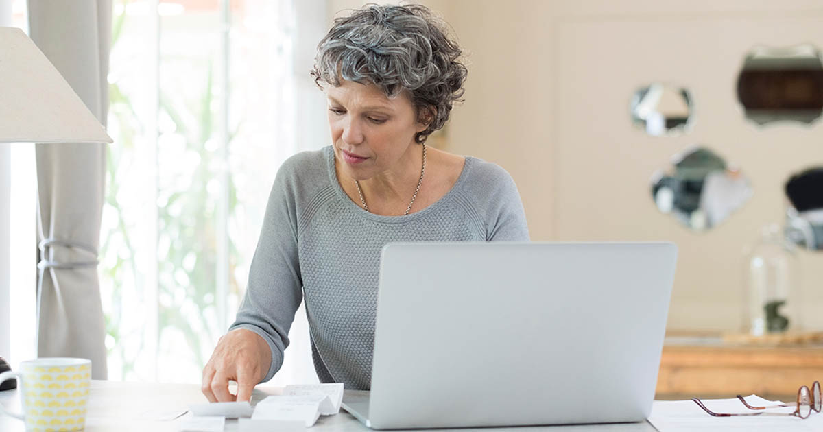 Mature woman looking at some papers while on her laptop